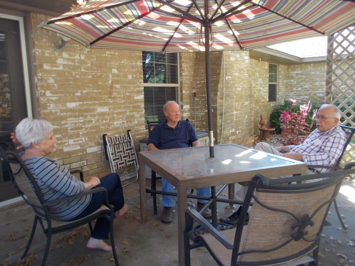 Martha, Perry, and John chatting on the patio