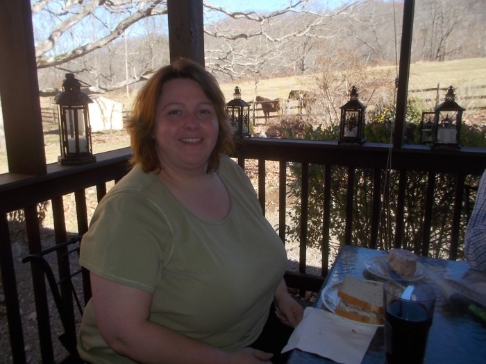 112916 Lise at breakfast on the porch, horses behind.JPG