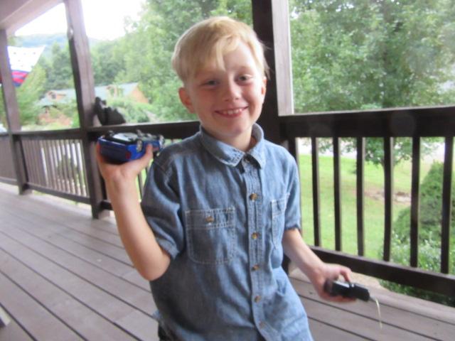 090918 Logan runs a radio car by his face.JPG