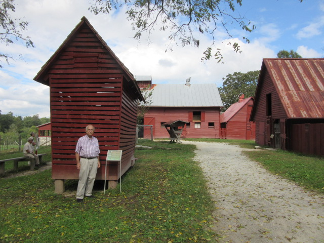 100818 John with goat farm buildings.JPG